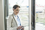 Businesswoman with digital tablet at the window - UUF006776