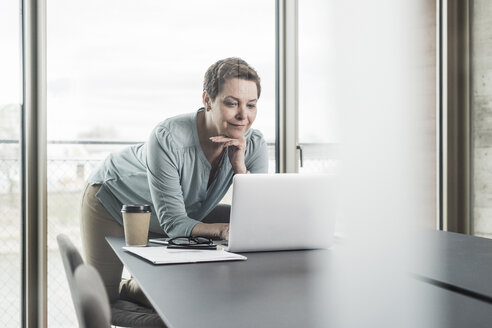 Businesswoman looking at laptop in office - UUF006797