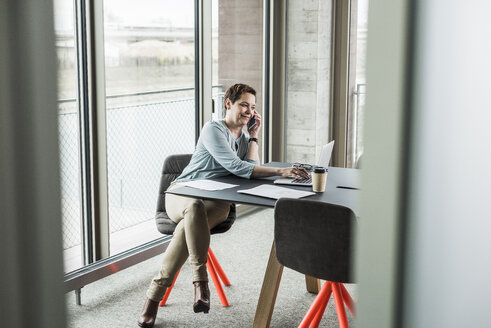 Businesswoman on cell phone using laptop in conference room - UUF006803