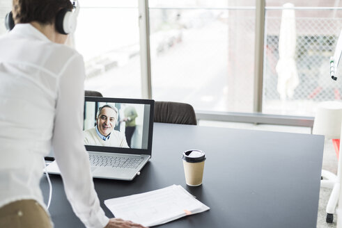 Businesswoman having a video conference in office - UUF006827