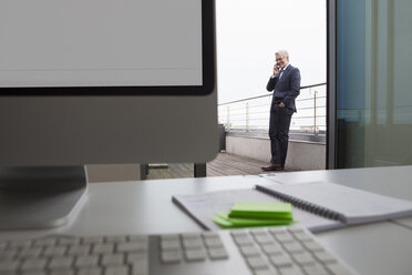 Successful businessman standing on office balcony talking on the phone - RBF004290