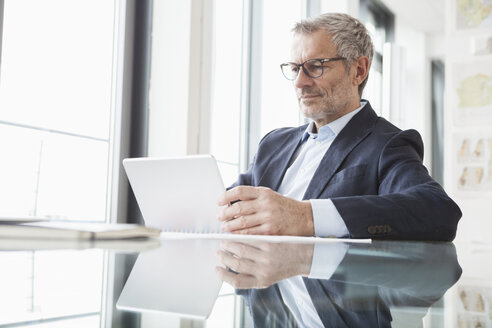 Successful businessman in his office using digital tablet - RBF004299