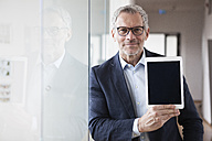 Successful businessman standing in his office holding digital tablet - RBF004326