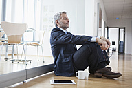Successful businessman sitting on floor taking a break - RBF004329