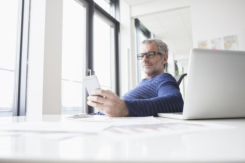 Mature man sitting in office with laptop, using smart phone - RBF004341