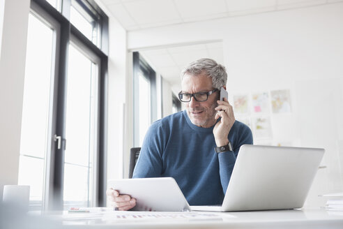 Mature man sitting in office using tablet pc and smart phone - RBF004347