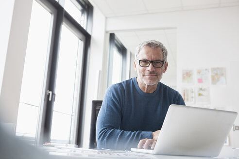Mature man sitting in office using laptop - RBF004350