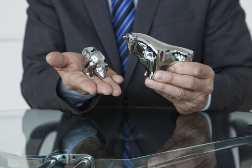 Businessman observing stock market, bull and bear figurines - RBF004362