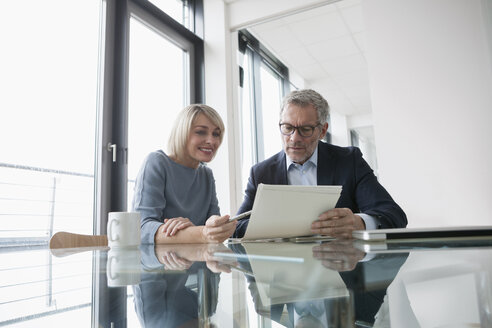 Businessman and woman working together in office discussing documents - RBF004383