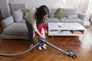 Mother showing her little daughter hoovering the floor - LITF000249