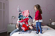 Mother and little daughter playing  with laundry on the bed - LITF000252
