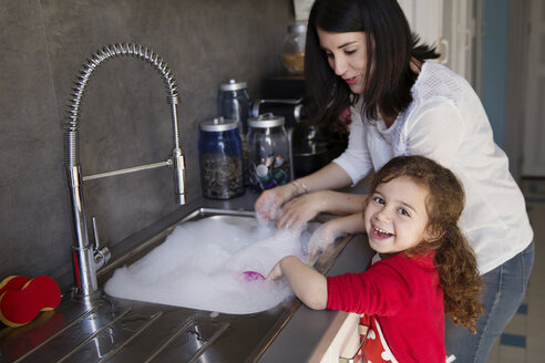 Portrait of little girl washing dishes together with her mother - LITF000255