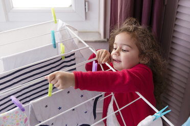 Little girl hanging out the laundry on a drying rack - LITF000258