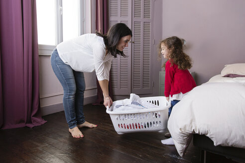 Mother and little daughter carrying  laundry basket together - LITF000261