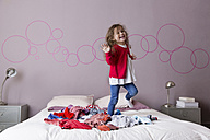 Little girl dancing on a pile of laundry on her parents' bed - LITF000264
