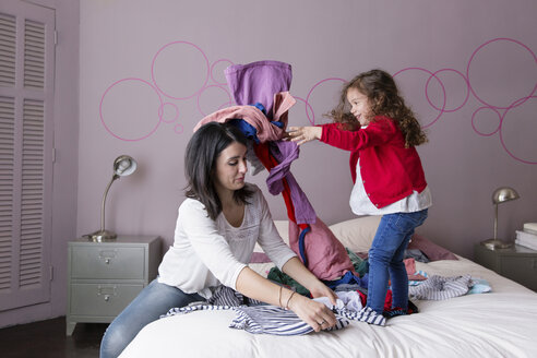 Mother folding clothes on the bed while her daughter throwing laundry at her - LITF000267