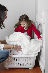 Mother and her little daughter filling tumble dryer with laundry - LITF000270