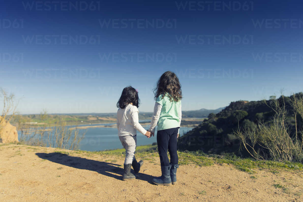 Spain, Burujon, back view of two little girls looking at a lake - ERLF000161 - Enrique Ramos/Westend61