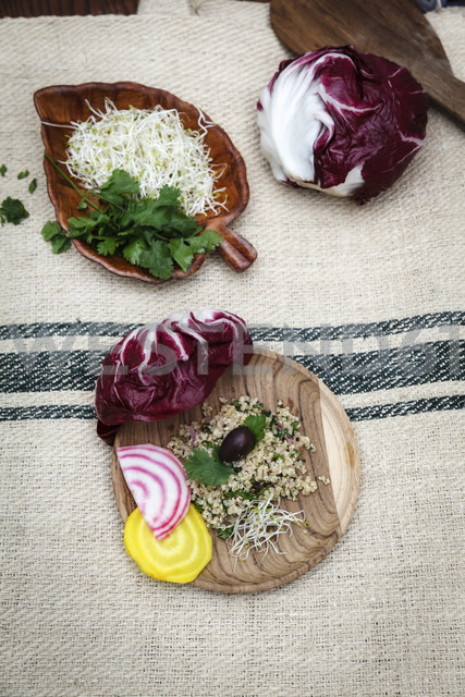 Quinoa salad, radicchio, beetroot, yellow and red on wooden plate - EVGF002913