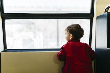 Back view of little boy on his first train ride looking through window - JRFF000534