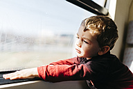 Portrait of little boy on his first train ride looking through window - JRFF000537