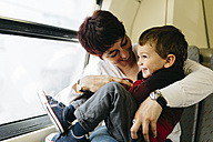 Happy little boy on his first train ride having fun with his mother - JRFF000540