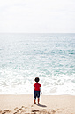 Back view of little boy standing on the beach looking at the sea - VABF000432