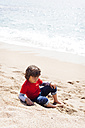 Little boy sitting on the beach at seafront - VABF000435