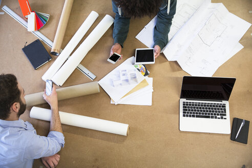 Two colleagues with portable devices surrounded by construction plans - FKF001777