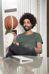 Creative professional balancing basketball at desk in office - FKF001831