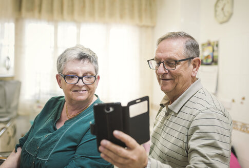 Senior couple looking at smartphone at home - EPF000067