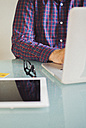 Man using laptop at desk, partial view - JPF000131