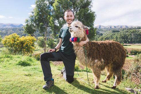 Peru, Cusco, portrait of happy tourist posing with llama - GEMF000860