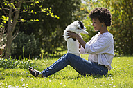 Young woman sitting on a meadow playing with her dog - MAUF000437