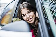 Brunette woman sitting in car looking through window - UUF006857