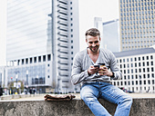 Young man sitting on wall reading text messages - UUF006860
