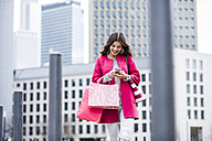 Young woman in the city using mobile phone - UUF006872