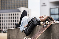 Young woman with skateboard resting on wall - UUF006902