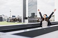 Young woman in the city wearing headphones, dancing - UUF006911