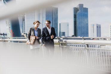 Young business couple walking on bridge, talking - UUF006947