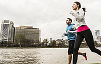 Young couple jogging by river - UUF006956