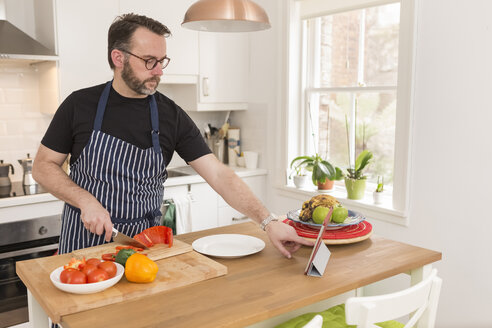 Man using digital tablet in his kitchen while preparing vegetables - BOYF000248