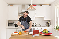 Man telephoning with smartphone while preparing vegetables in the kitchen - BOYF000254