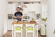 Man using digital tablet while preparing food in the kitchen - BOYF000257