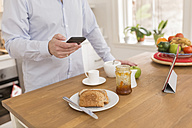 Man standing at breakfast table in the kitchen using smartphone, partial view - BOYF000266