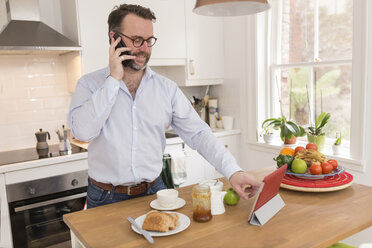 Man standing at breakfast table  in the kitchen telephoning with smartphone while using digital tablet - BOYF000269