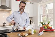 Portrait of man in kitchen pouring espresso into a cup - BOYF000272