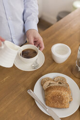 Man pouring milk into coffee cup at breakfast table, partial view - BOYF000275
