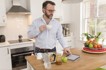 Man with cup of coffee standing in the kitchen using digital tablet - BOYF000278