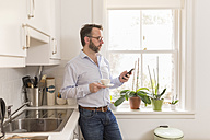 Man standing in the kitchen with cup of coffee looking at his smartphone - BOYF000281